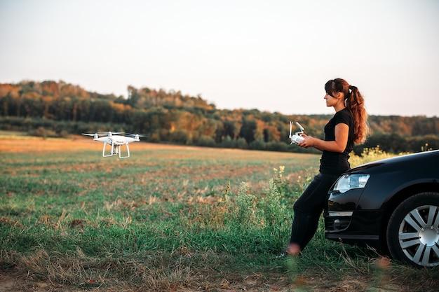 Una donna in piedi vicino all'auto lancia un drone. volo con drone in campo giallo