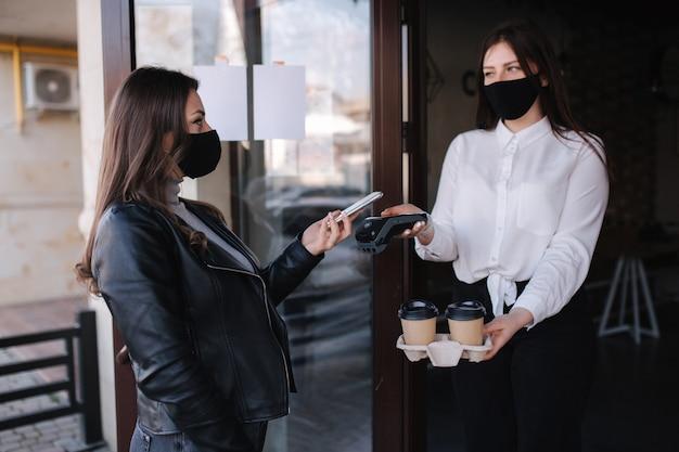Donna in piedi all'aperto da bar e pagare con lo smartphone durante la mano del cassiere di pandemia covid