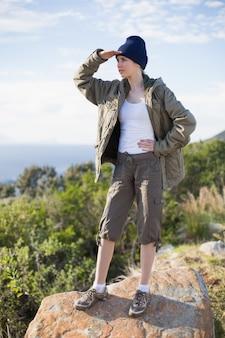Donna in piedi su una roccia che guarda alla distanza