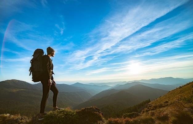 La donna in piedi sulla roccia con un pittoresco tramonto