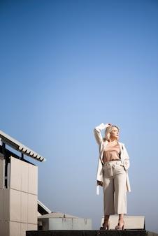 Donna in piedi sul tetto in una soleggiata giornata autunnale.