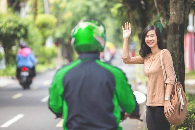 Donna che sta sul marciapiede che ordina il taxi del motociclo