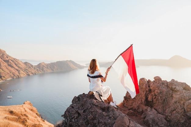 Una donna in piedi in cima alle colline e con in mano la bandiera dell'indonesia a padar island labuan bajo