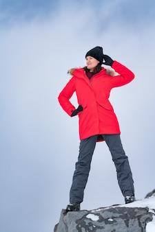Donna in piedi sulla cima del picco di montagna sullo sfondo del cielo con nuvole drammatiche concetto di viaggio travel