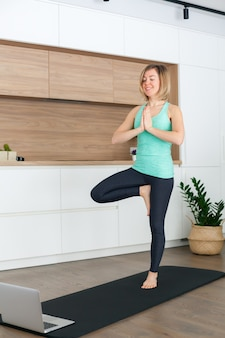 Donna in piedi in una posa ad albero mentre si fa yoga online a casa