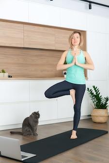 Donna in piedi nella posa della struttura ad albero mentre si fa yoga online a casa