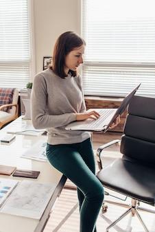 Donna in piedi che scrive sulla tastiera di un notebook nel suo ufficio