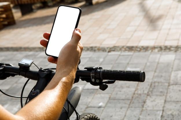 Donna in piedi con la bicicletta e mostra il telefono con schermo bianco vuoto