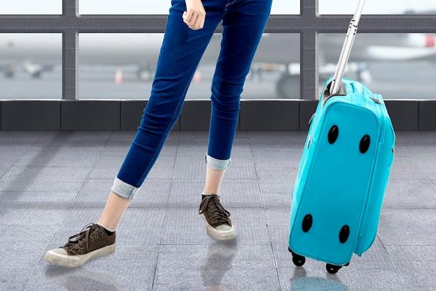 La donna in piedi con una valigia sul terminal dell'aeroporto