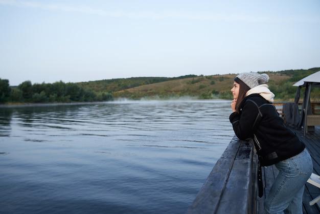 Donna in piedi sul molo in legno e guardando la natura