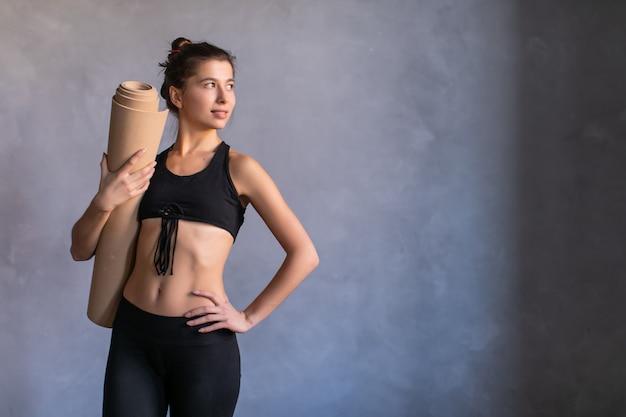 Donna in piedi a allenamento o lezione di yoga con tappetino fitness nel suo hads. copia spazio su sfondo scuro