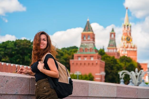 Una donna si trova su un ponte con uno spazio sul cremlino di mosca, l'attrazione principale della russia