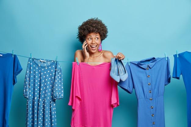 La donna sta vicino allo stendibiancheria con abiti appesi tiene scarpe blu col tacco alto ha una conversazione telefonica guarda positivamente lontano pose al coperto