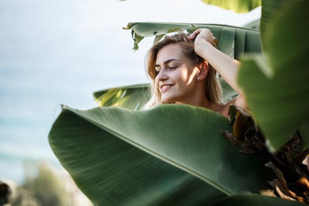 Una donna sta vicino alle foglie di banana verde sull'isola. alberi tropicali