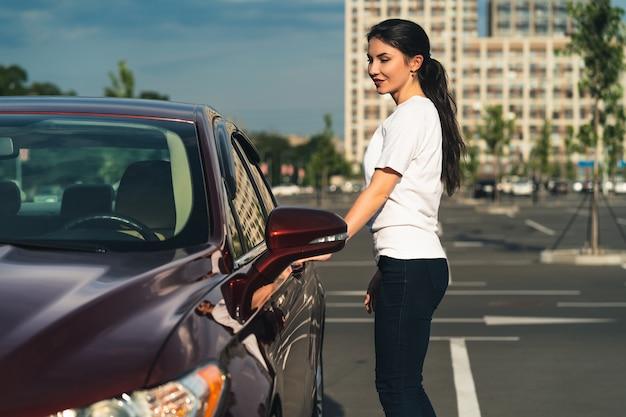 La donna sta vicino alla macchina nuova nel parcheggio