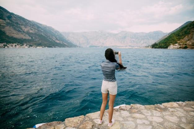 Una donna si trova sul molo e scatta foto della baia di kotor.