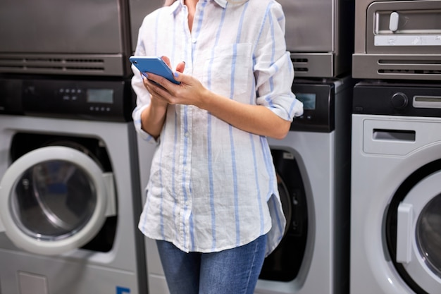 La donna sta accanto alla lavatrice utilizzando il telefono cellulare, in attesa della fine del lavaggio. femmina irriconoscibile ritagliata in casa di lavaggio