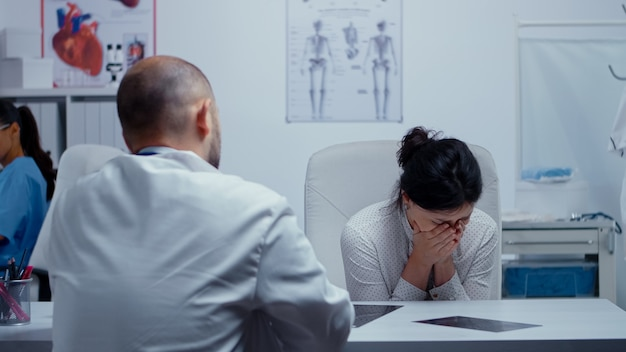La donna inizia a piangere dal dottore dopo aver sentito cattive notizie sulla salute di lei o di altre persone care. brutte notizie sul paziente terminale. cancro o altro concetto di malato terminale