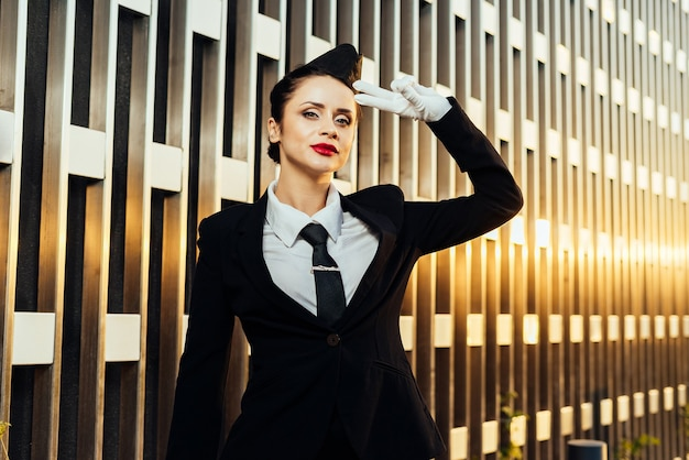 Hostess della donna in uniforme che posa sulla priorità bassa della costruzione