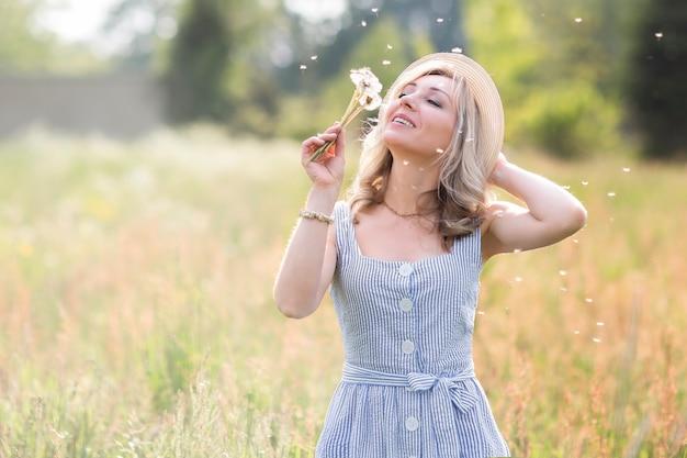 Donna con un cappello di paglia in un campo di fiori con un bouquet di fiori selvatici