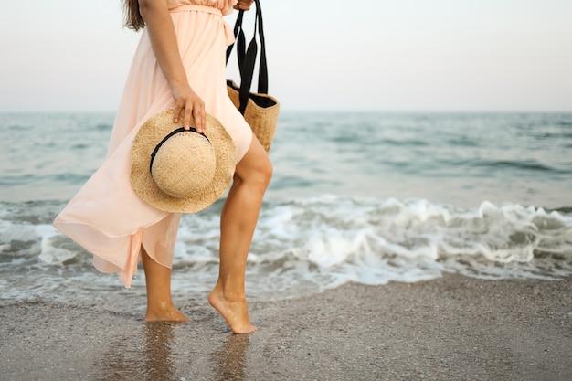 Donna in cappello di paglia e vestito rosa su una spiaggia tropicale con borsa marrone.
