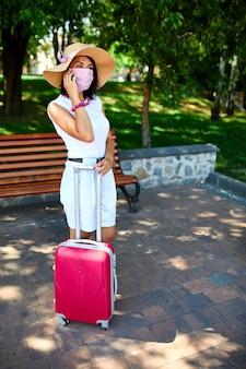 Donna con cappello di paglia e maschera protettiva rosa, nel parco all'aperto con una valigia, parlando su un cellulare, vita durante la pandemia di coronavirus, apertura del viaggio aereo, concetto di viaggio.