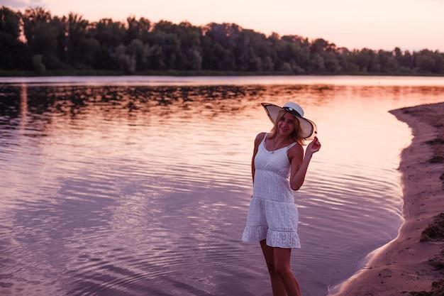 Una donna con un cappello di paglia posa una bella giovane bionda snella in un abito di pizzo bianco in piedi sul ri...