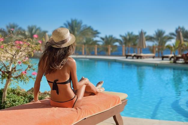 Donna in un cappello di paglia che si rilassa su un divano vicino ad un lussuoso hotel egitto piscina, tempo di concetto di viaggiare