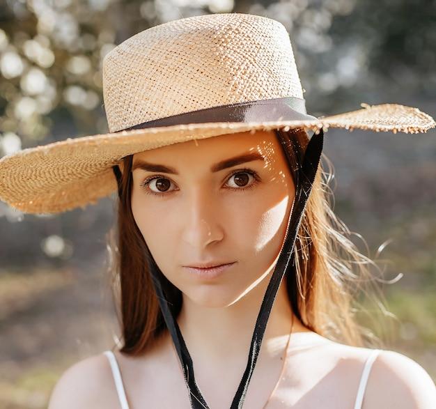Donna in un cappello di paglia in primavera nel parco
