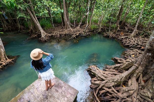 Una donna, flusso di acqua e bella radice di alberi a thapom klong song nam, krabi, thailandia