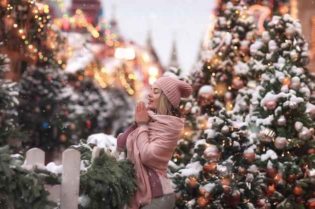 Una donna per strada con una sciarpa rosa il giorno di capodanno sullo sfondo di un albero di natale decorato