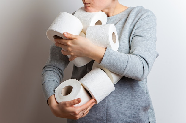 La donna allunga in avanti molti rotoli di carta igienica.