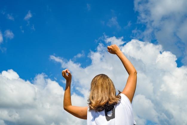 Una donna allunga le mani al cielo