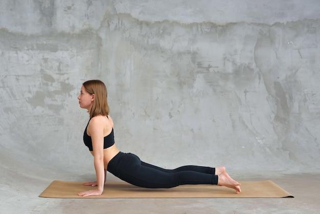 Donna che si estende in posa cobra, facendo esercizio bhujangasana, praticando yoga.