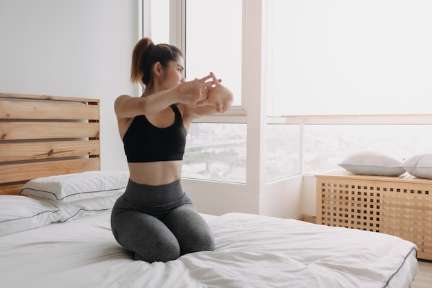 Donna che si allunga e si rinfresca dopo l'allenamento nel suo appartamento