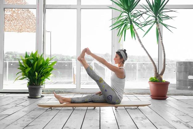Donna che allunga la gamba su una tavola sup indoor.
