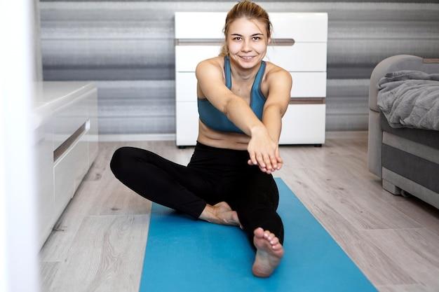 Donna che allunga la gamba sulla stuoia di yoga blu a casa nel soggiorno