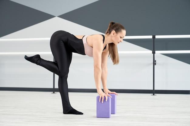 Donna che allunga le gambe utilizzando piccoli blocchi