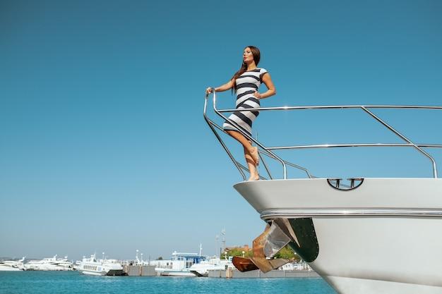 Donna in un abito a righe in piedi su uno yacht