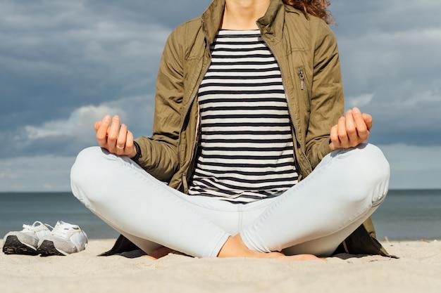 La donna in t-shirt a righe e il cappotto verde è seduta in posizione di meditazione sulla spiaggia