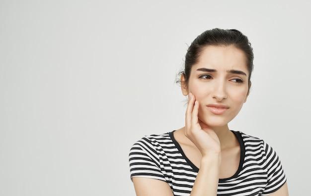 Donna in maglietta a strisce che tiene il malcontento di dolore di problemi dentali del fronte