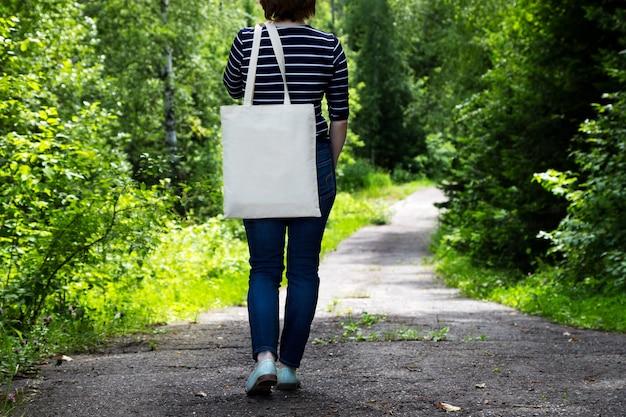 Donna in maglietta a righe che trasporta mockup di borsa della spesa riutilizzabile vuota.