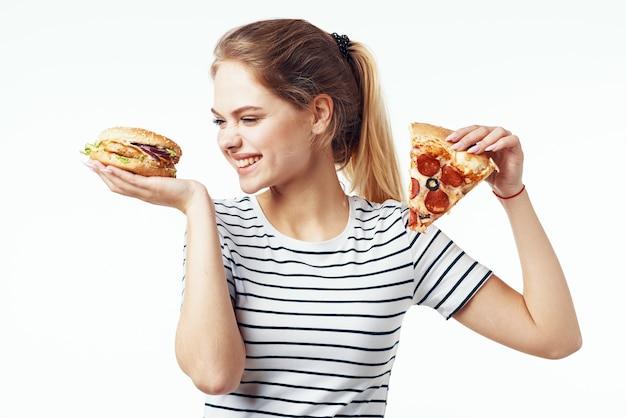 Donna in maglietta a strisce che mangia fondo leggero della dieta degli alimenti a rapida preparazione della pizza