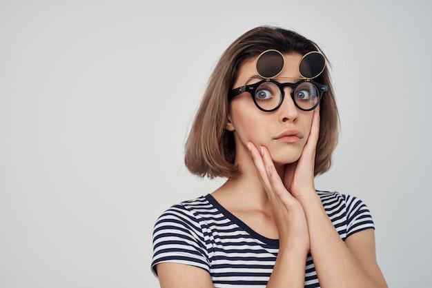 Donna in maglietta a righe moda occhiali studio in posa