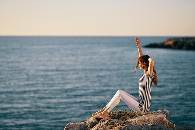 La donna in una maglietta a righe ha alzato le mani vicino al mare in piselli