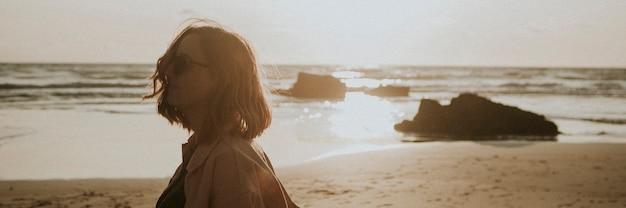 Donna che passeggia sulla spiaggia al tramonto