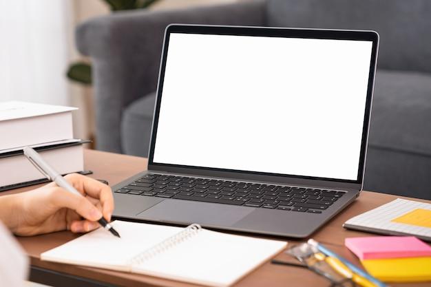 Donna che studia e-learning sul computer portatile con uno schermo bianco mockup sul tavolo di legno.