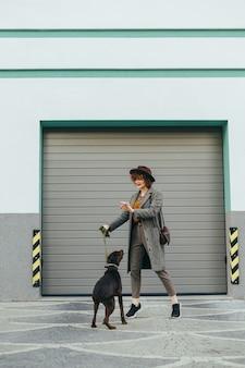 La donna in vestiti alla moda e cappello si diverte con un cane in passeggiata