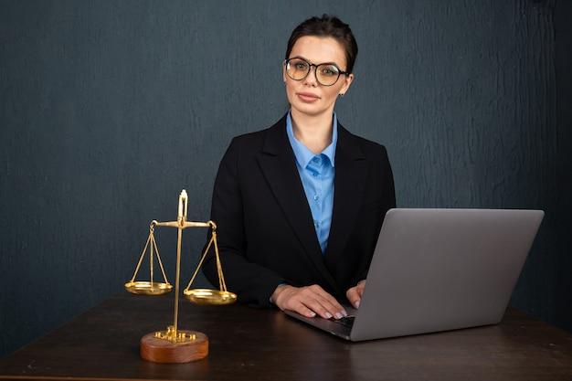 Donna in occhiali alla moda iscritto notaio nel libro di testo durante l'apprendimento in linea sul computer portatile