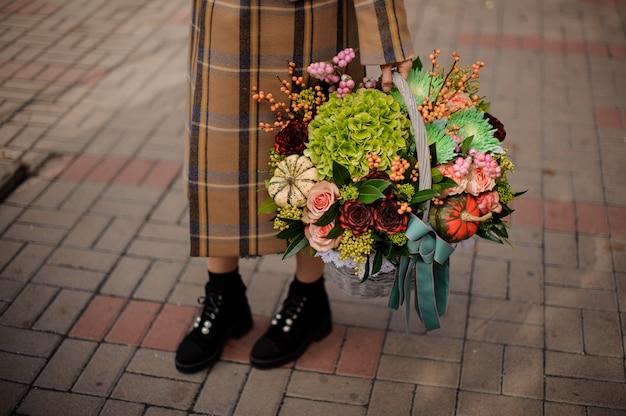 Donna in elegante plaid lungo cappotto in possesso di un grande cesto di vimini di bella composizione autunnale di fiori
